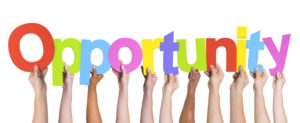 Multiethnic hands hold up the word Opportunity