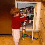 An autistic boy - autism - carefully stacks cans.
