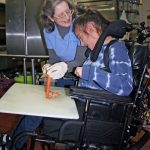 Young woman with cerebral palsy loves community-based cooking class.