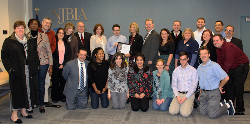 Employees of NJBA gathered around agency CEO Jack Mudge and one-time intern Raul Rodriguez