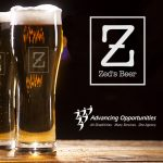 Two glasses of tasty Zed's Beer craft brew on wooden table and bar lights background.
